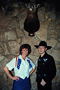 Cowboy and cowgirl pose next to last week's dinner, deer head, Lakeside, U.S.A, 1998.