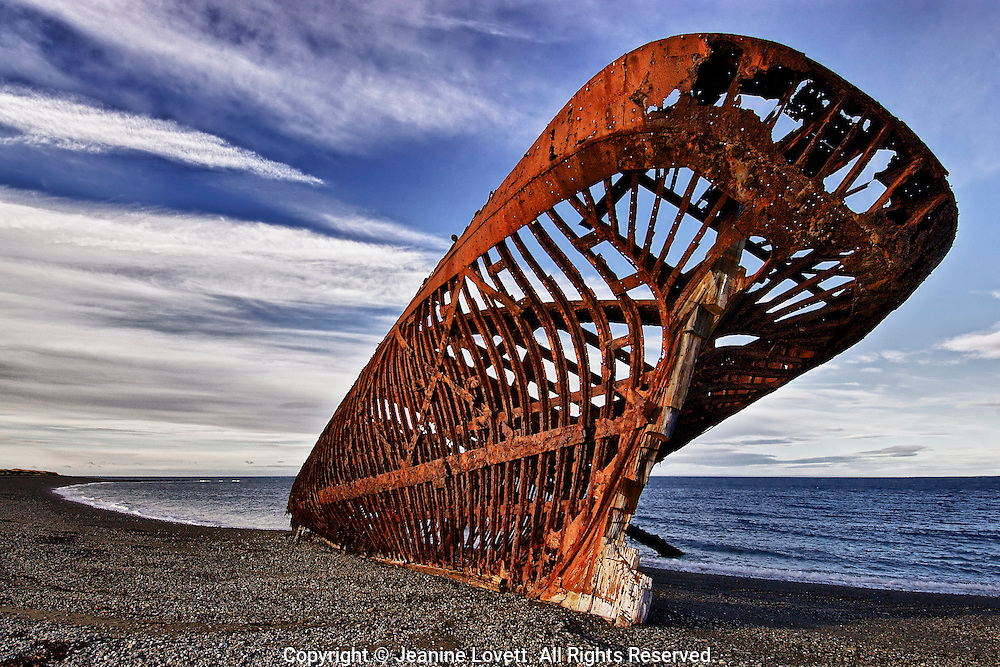 Rusted skeleton of a ship rests on a gravel beach.