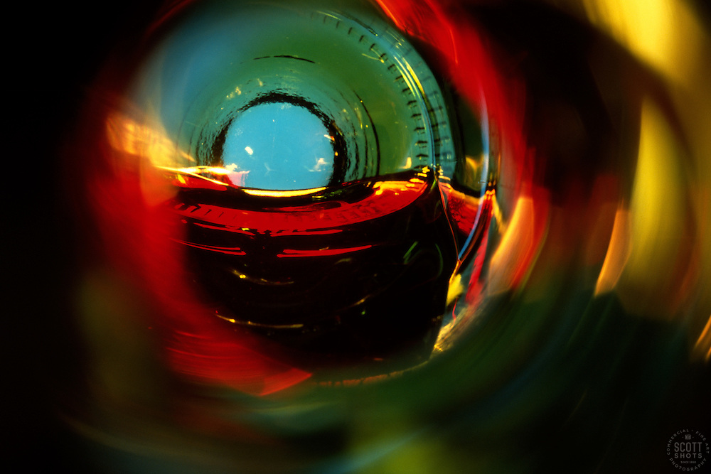 """""""Beauty at the Bottom: Red Wine 2""""- This image is a photograph of a wine bottle shot right down the mouth of the bottle. A television provides the main light source."""