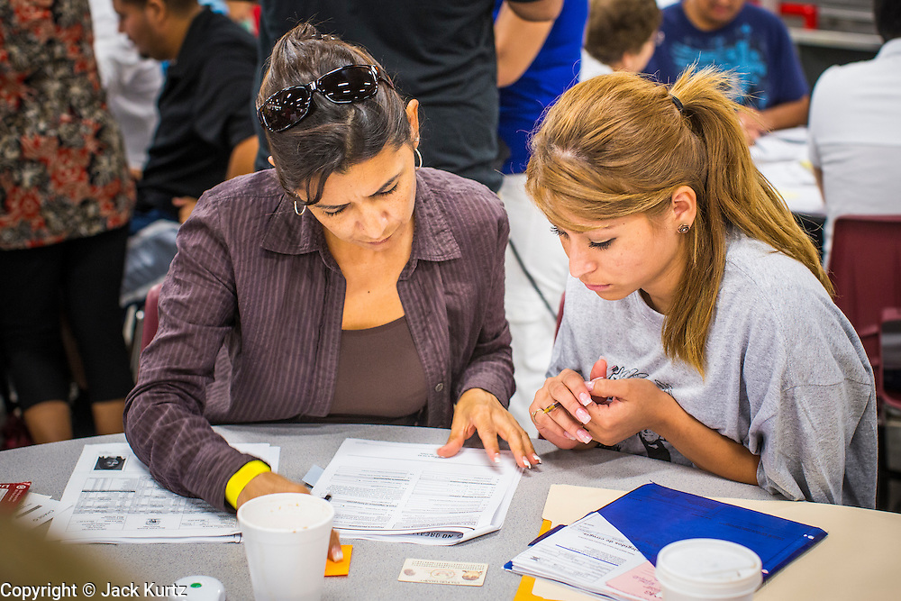"""25 AUGUST 2012 - PHOENIX, AZ:  A volunteer (left) helps a woman complete the paperwork necessary for her to apply for deferred action status at a workshop in Phoenix. Hundreds of people lined up at Central High School in Phoenix to complete their paperwork to apply for """"Deferred Action"""" status under the Deferred Action for Childhood Arrivals (DACA) program announced by President Obama in June. Volunteers and lawyers specialized in immigration law helped the immigrants complete the required paperwork. Under the program, the children of undocumented immigrants brought to the US before they turned 16 years old would not be subject to deportation if they meet a predetermined set of conditions.   PHOTO BY JACK KURTZ"""