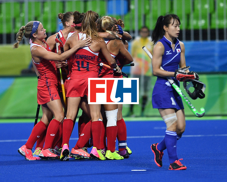 USA team members celebrate a goal as Japan's Akane Shibata walks past during the women's field hockey USA vs Japan match of the Rio 2016 Olympics Games at the Olympic Hockey Centre in Rio de Janeiro on August, 10 2016. / AFP / MANAN VATSYAYANA        (Photo credit should read MANAN VATSYAYANA/AFP/Getty Images)