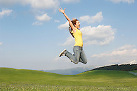 Woman jumping for joy in mountain meadow side view