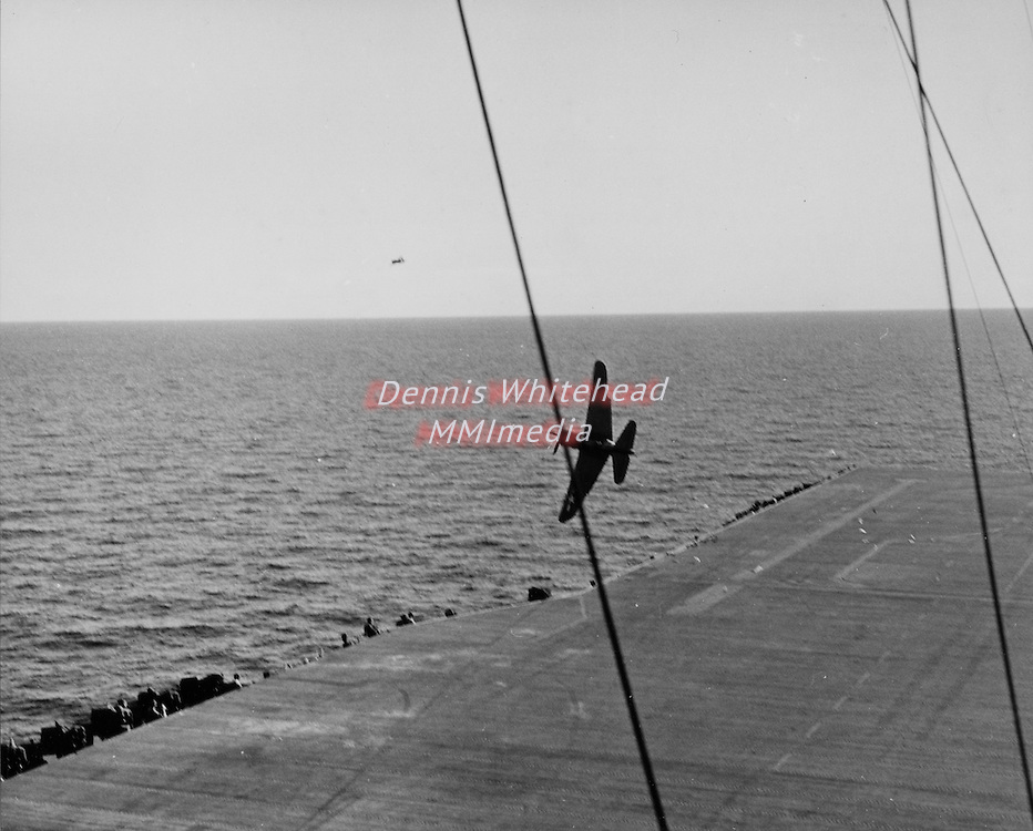 October 26, 1944 - Crash of SB2C Helldiver - (nine picture sequence) - An SB2C Helldiver attempts a take-off and then goes over the port side of the USS Bennington in the Gulf of Paria, off the coast of Trinidad. The pilot was Ens. D.B. Hope (A-1) USNR, and Air Crewman C.R. Crowley, ARM3c, V-6, USNR. picture sequence) - 1/8 - An SB2C over the port side of the USS Bennington in the Gulf of Paria, off the coast of Trinidad. The pilot was Ens. D.B. Hope (A-1) USNR, and Air Crewman C.R. Crowley, ARM3c, V-6, USNR.