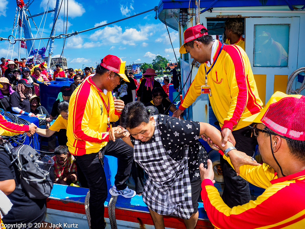"02 JUNE 2017 - SAMUT SAKHON, THAILAND: Devotees of the City Pillar Shrine get off a boat after the parade on the Tha Chin River. The Chaopho Lak Mueang Procession (City Pillar Shrine Procession) is a religious festival that takes place in June in front of city hall in Samut Sakhon. The ""Chaopho Lak Mueang"" is  placed on a fishing boat and taken across the Tha Chin River from Talat Maha Chai to Tha Chalom in the area of Wat Suwannaram and then paraded through the community before returning to the temple in Samut Sakhon. Samut Sakhon is always known by its historic name of Mahachai.      PHOTO BY JACK KURTZ"