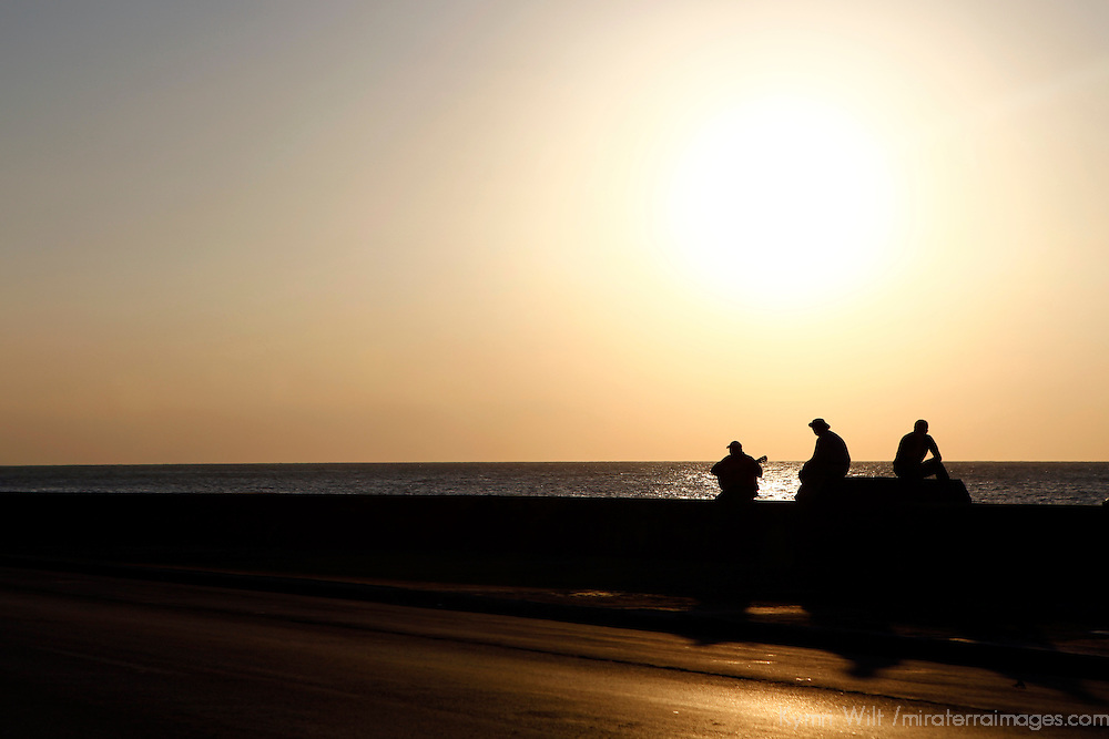 Central America, Cuba, Havana. Three Cubans and a guitar at sunset on the Malecon, Havana.