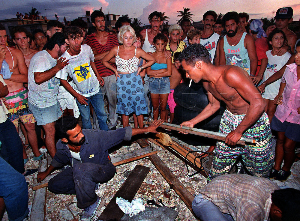 8/1994-Al Diaz/Miami Herald--In 1994 Cuban balseros turned the tiny fishing village of Cojimar into a major point of embarkation for thousands seeking a better life. Here, Armando Alarcon Ramirez, holding a stick on right, helps build his homemade raft before his departure from Cojimar, Cuba.
