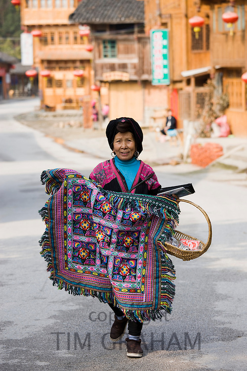 Yao minority group Chinese woman selling traditional rug in Ping An street, near Guilin, China