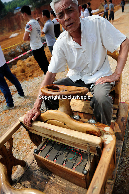 LIUZHOU, CHINA - MAY 19: (CHINA OUT) <br /> <br /> Wooden Three-wheeled Vehicle<br /> <br />  Wei Guirong shows off his home-made three-wheeled vehicle to villagers on May 16, 2014 in Liuzhou, Guangxi Province of China. Wei Guirong, 66, has made three wooden three-wheeled vehicles for grandchildren, and the vehicles are made entirely from wood, apart from the engine, wheels and some electronic parts. He was in charge of maintaining agricultural machinery when he was younger.  <br /> &copy;Exclusivepix