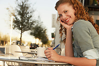 Young woman writing at outdoor cafe portrait