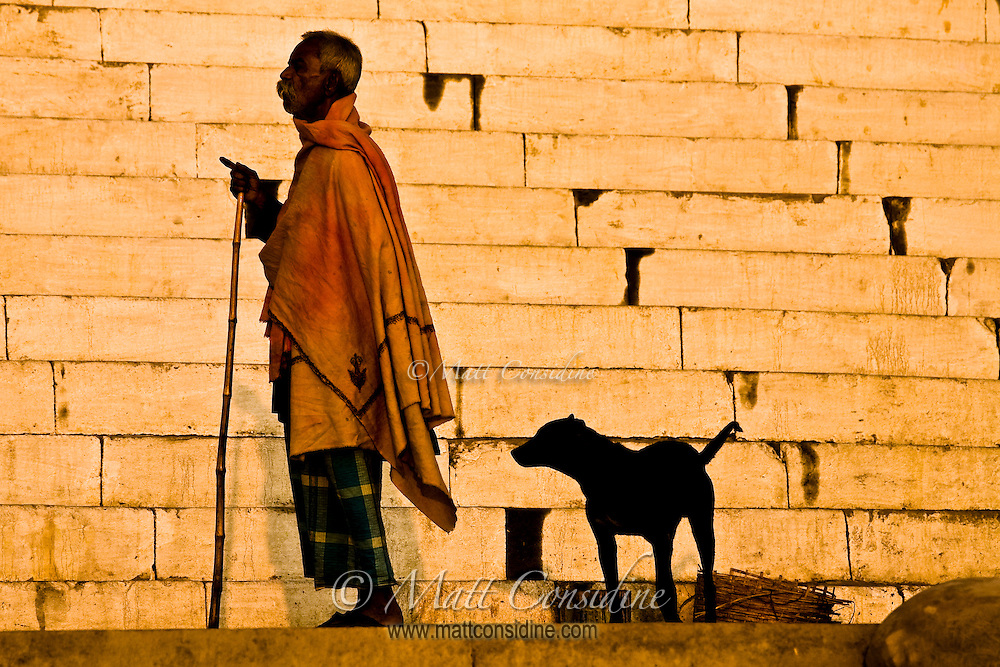Old man holding walking stick and a black dog behind him on a ghat in Varanasi, Uttar Pradesh India.<br /> (Photo by Matt Considine - Images of Asia Collection)