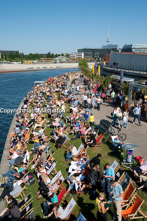 Many people sitting by the Spree River at outdoor cafe and bars in Mitte central Berlin 2009