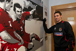 SWANSEA, WALES - Monday, March 1, 2010: Wales' Andy Doorman autographs a painting before training at the Liberty Stadium ahead of the international friendly match against Sweden. (Photo by David Rawcliffe/Propaganda)