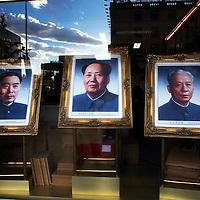BEIJING, NOV. 8, 2012 : ein Portrait von Mao Zedong , flankiert von Zhou Enlai ( L) und Liu Shaoqi ( R) im Schaufenster eines Geschaeftes in einer Einkaufsstrasse .