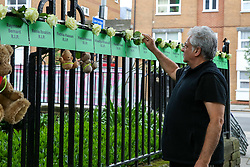 © Licensed to London News Pictures. 14/06/2019. London, UK. A family member of a victim puts a white flower on the names of people who lost their lives on a railings on a block of flats to commemorate the second anniversary of the Grenfell Tower fire service. On 14 June 2017, just before 1:00 am a fire broke out in the kitchen of the fourth floor flat at the 24-storey residential tower block in North Kensington, West London, which took the lives of 72 people. More than 70 others were injured and 223 people escaped. Photo credit: Dinendra Haria/LNP