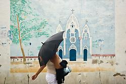 Centro da cidade de Delmiro Gouveia, em Alagoas. Mulher passando em frente a mural representando a Igreja da cidade/ Woman with unbrella crossing in front of a wall painted, representing the city of Delmiro Gouveia.Foto Marcos Issa