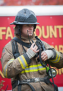 A firefighter clips his radio to his jacket.