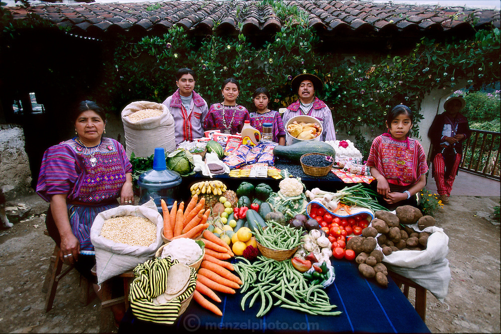 (MODEL RELEASED IMAGE). The Mendoza family and a servant in their courtyard in Todos Santos Cuchumatán, Guatemala, with a week's worth of food. Between Fortunato Pablo Mendoza, 50, and Susana Pérez Matias, 47, stand (left to right) Ignacio, 15, Cristolina, 19, and a family friend (standing in for daughter Marcelucia, 9, who ran off to play). Far right: Sandra Ramos, 11, live-in helper. Not present: Xtila, 17, and Juan, 12. Cooking methods: gas stovetop, wood stove. Food preservation: refrigerator. /// The Mendoza family is one of the thirty families featured in the book Hungry Planet: What the World Eats (p. 156). Food expenditure for one week: $75.70 USD. (Please refer to Hungry Planet book p. 157 for the family's detailed food list.)