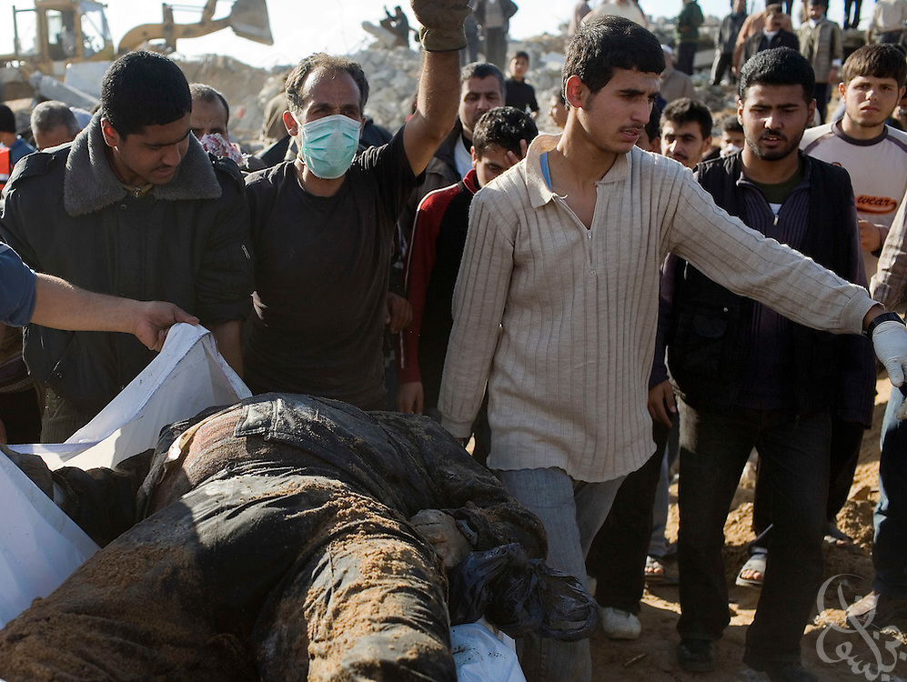 Relatives carry the body of one of the 28 members of the Samouni family they dug out from their flattened home January 18, 2009 in the Zeitoun district of Gaza. All 28 members of the family were killed by an apparent airstrike on their home during the 21 day Israeli operation in Gaza and finally dug out of the rubble today by extended family members following a ceasefire announcement by the Israelis last night.