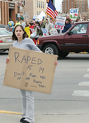 Lone woman holds a sign in protest of the  pending anti-abortion legislation in South Dakota. Downtown Rapid City, 2007.