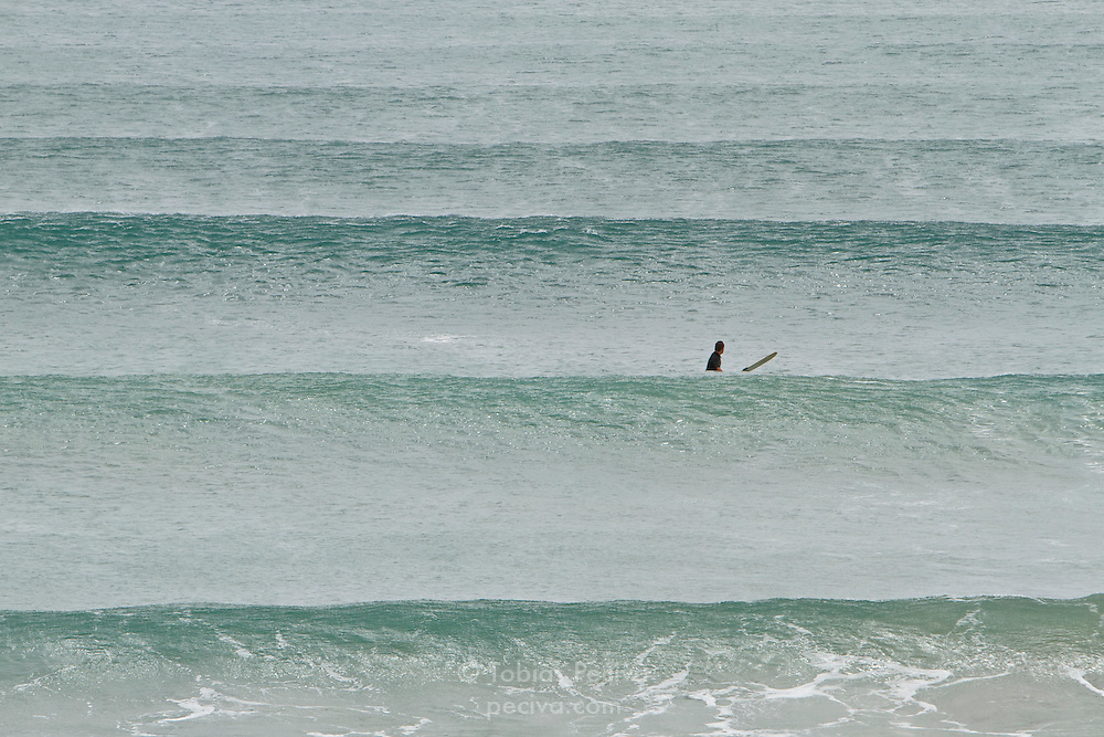 Lone surfer waiting for waves in Ngunguru Bay, near Pataua, Northland, New Zealand.