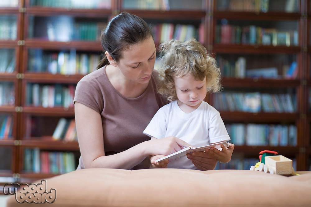 Brunette woman teaches blonde toddler how to read