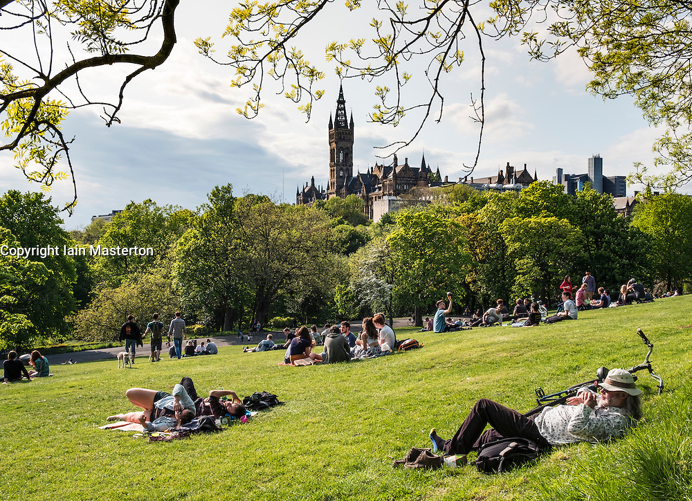 Students relaxing on lawns of Kelvingrove Park with Glasgow university in the distance in Scotland, United Kingdom