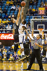 Jan 26, 2016; Morgantown, WV, USA; West Virginia Mountaineers forward Jonathan Holton (1) and Kansas State Wildcats forward Dean Wade (32) jump for the tip ball at the WVU Coliseum. Mandatory Credit: Ben Queen-USA TODAY Sports
