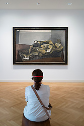 Visitor looking at Picasso painting Dora Maar with Green Fingernails at Berggruen Museum in Berlin Germany