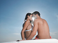 Young couple embracing on cushions outdoors face to face sun breaking through back view