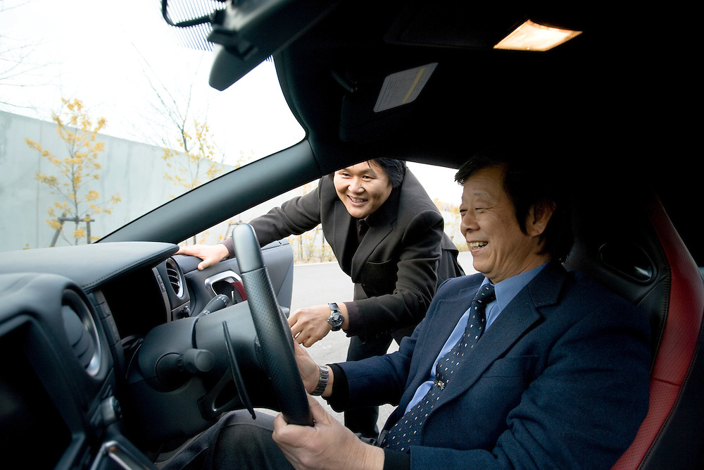 The chief engineer and project planner Kazutoshi  Mizuno (blue suit) -,  chief designer   Hiroshi Hasegawa (brown suit) and   who are  responsible for the  design of  the  GT-R sports car..