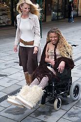 Carer and young woman with Cerebral Palsy shopping,