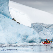 A pair of kayakers in a tandem kayak navigate a narrow channel between large icebergs at Melchior Island on the Antarctic Peninsula.