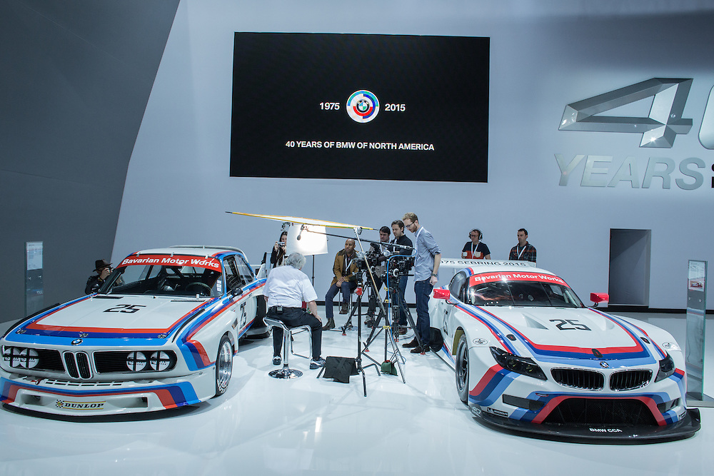 New York, NY - 1 April 2015. Former racecar driver Ronnie Peterson being interviewed while sitting between two BMW racecars, a 3.0 CSL on the left and a Z4 GTLM on the right.