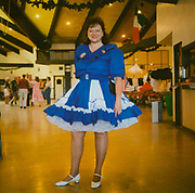 A woman standing in a hall in her line, country dancing outfit USA