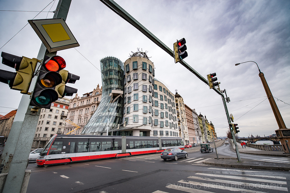 Norman Foster Dancing House in Prague looks over street life passing by.