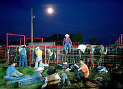 Rodeo cowboys relax during some down time under a full moon