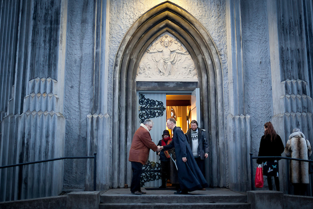"The priest greets parishoners after Christmas Day mass at  Landakotskirkja (also named Basilika Krists konungs or in English ""The Basilica of Christ the King"") in Reykjavik, Iceland on December 25, 2013. Only 3% of Icelanders are Catholic."