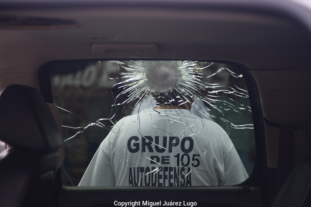 Self defense force member in Tepalcatepec, seen through the window of a shot-up armored truck they group said they seized from the Knights Templar drug gang as they fled town.