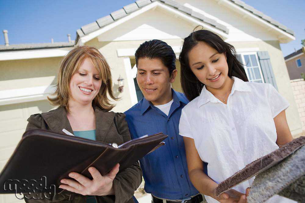 Young couple buying house, signing contract