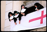 Nuns stand on balcony admiring parading celebrants during Moors & Christians fest; Alcoy. Spain