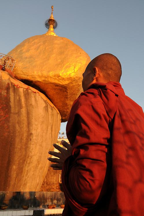 Monk praying before the golden rock, Kytiku, Myanmar, Asia