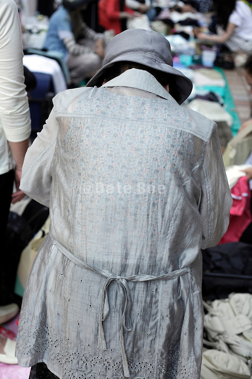 back view of woman looking for clothing at an outdoors flee market