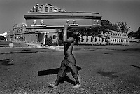A man carries a coffin on his head past Haiti's army barracks as he heads toward the hospital to bury his dead son.