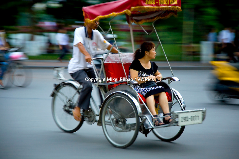 woman in a traditional transport.<br /> Hanoi, Vietnam.