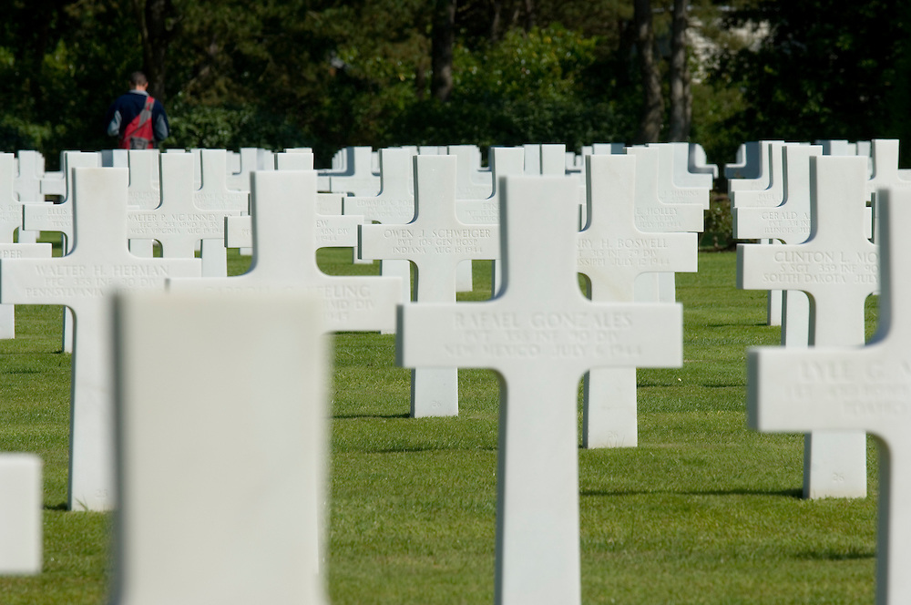 Vistors walk amongst the grave stones of the American war cemetery at St Laurent, France. 9387 US servicemen are buried there.