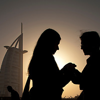 United Arab Emirates, Dubai, Tourists exchange cameras while taking snapshots near Burj al-Arab Hotel at sunset along Jumeirah Beach