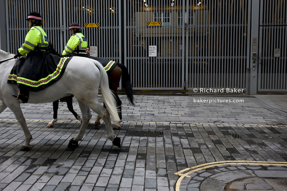 Mounted City of London police officers on their horses patrol back streets of the Square Mile, London's financial district.