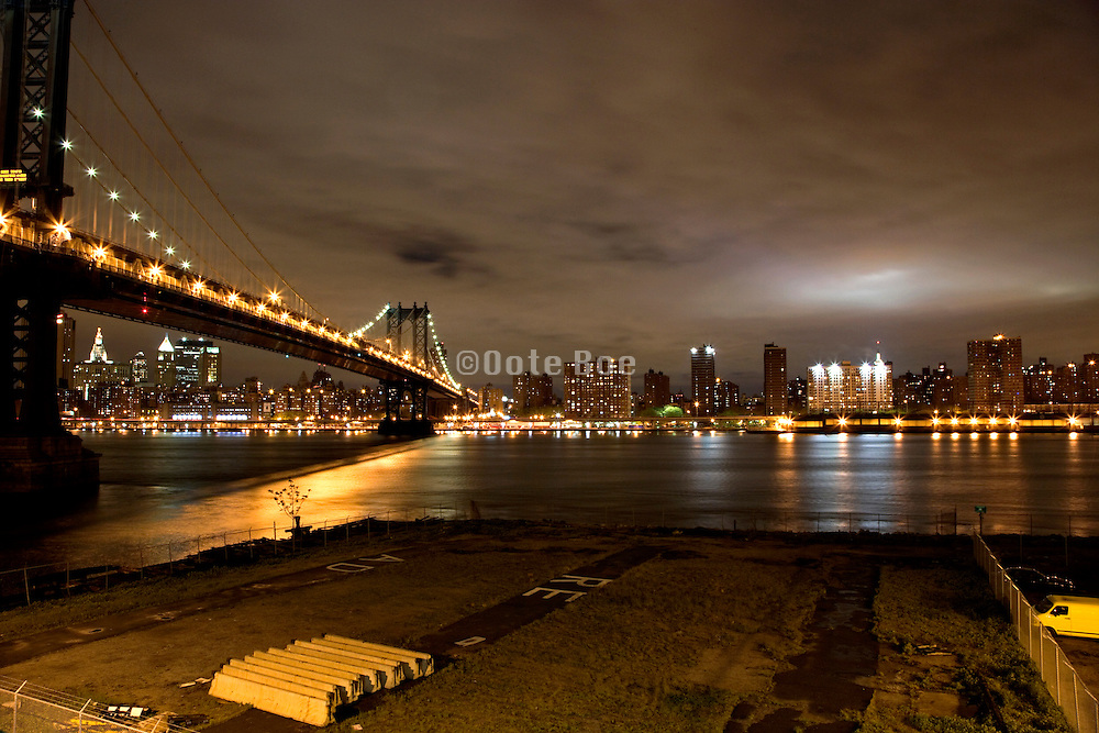 night view of Manhattan with Manhattan Bridge East River and in the distance The Empire State Building