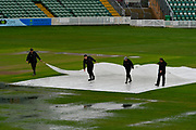 Ground staff removing protective covers from the wicket square to let it dry at after heavy overnight rain left the outfield waterlogged and flooded at Somerset County Cricket Club at the Cooper Associates County Ground, Taunton, United Kingdom on 11 April 2018. Picture by Graham Hunt.