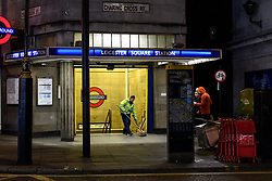 © Licensed to London News Pictures. 20/03/2020. London, UK. A street cleaner sweeps outside a deserted Leicester Square station. The West End was left unprecedentedly empty on Friday night following the government's announcement that all bars, pubs and restaurants must be closed immediately in the latest step to curb the coronavirus outbreak.  Photo credit: Guilhem Baker/LNP
